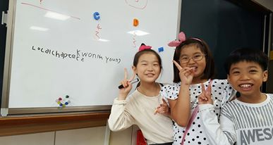 Students writing their Korean names on the board with the help of Google Translate
